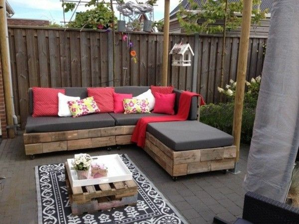 Wohlfühloase draußen schaffen Sofa aus Paletten selber gemacht bunte Wurfkissen Teppich - Kaffeetisch
