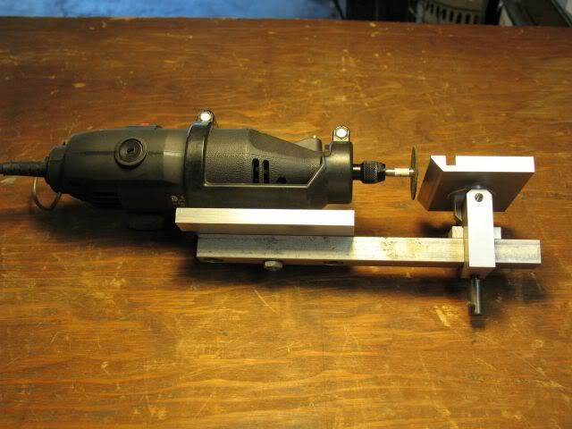 Getting the most from your Dremel by mklotz - The Dremel is a wonderful, versatile tool in the hobbyist's workshop. While it's meant to be a hand-held tool, I often find it far more comfortable to bring the work to the tool rather than vice-versa.To that end, I built this jig to hold the tool.The plastic grip that clamps the Dremel was removed from a Dremel router attachment*. Without modification, it was attached to a baseplate - thus it can be returned to the router jig when nee