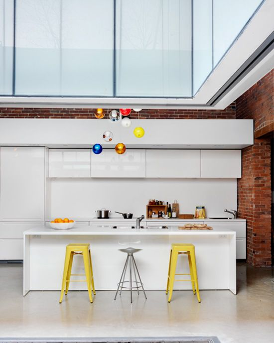 white kitchen with yellow stools in a Vancouver loft