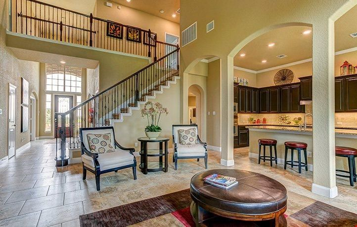 A graceful staircase leads to an open second-floor walkway that overlooks this great room. The Onyx plan, a new home from Village Builders at Johnson Ranch - Texas Reserve. Bulverde, TX.