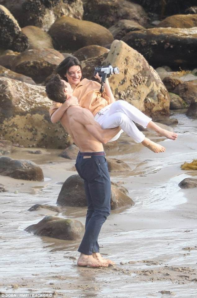 Now that's a fun day at work! Kendall Jenner is swung around by a shirtless hunk as she films on a beach in Malibu on Tuesday