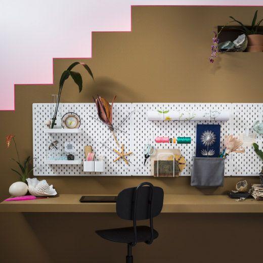 Una oficina doméstica con varios tableros blancos y accesorios de acero lacado en blanco (estantes, recipientes, clips, ganchos, portarrollos, etc.).