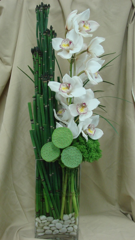 This is an arrangement featuring pods, horsetail and white cymbidium orchids.  See our entire selection at www.starflor.com.  To purchase any of our floral selections, as gifts or décor, please call us at 800.520.8999 or visit our e-commerce portal at www.Starbrightnyc.com. This composition of flowers is generally available for same day delivery in New York City (NYC). RE037