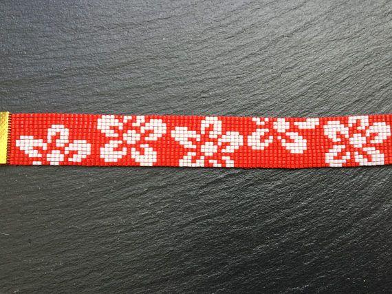 Handgeweven kralenarmband met Miyuki kralen 11/0 in rood en grote witte bloemen. Lengte 16,5 cm met goudkleurige sluiting en een verlengketting van 5 cm. Breedte: 2 cm. Ook verkrijgbaar in het paars (zie foto) of een andere achtergrondkleur op verzoek.