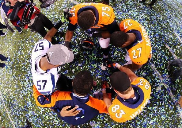Seattle Seahawks linebacker Mike Morgan (# 57) prays with members of the Denver Broncos after his team handed them a devastating 43-8 loss in the NFL's Super Bowl 2014 on Sunday