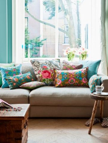 Bright colored floral or otherwise patterned pillows on neutral colored couch