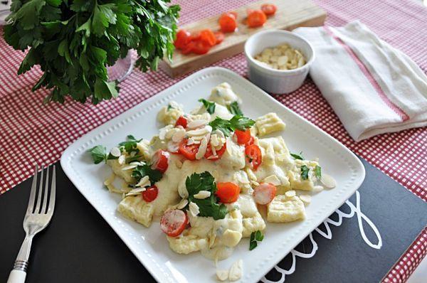 Gnocchi z sosem serowym, sos:    250 ml mleka    1 łyżka mąki    25 g masła    szczypta gałki muszkatołowej    ok. 60-80 g dojrzałego sera gorgonzola    garść pomidorków koktajlowych    pęczek pietruszki    garść prażonych płatków migdałowych (opcjonalnie)    sól i pieprz