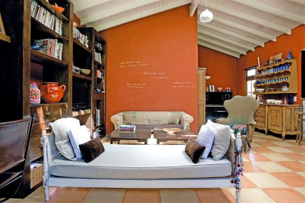 En el hall de recepción, una cama pintada con respaldo en esterilla (Anticuarios 202) y dos sillones clásicos con fundas hechas por la dueña de casa..