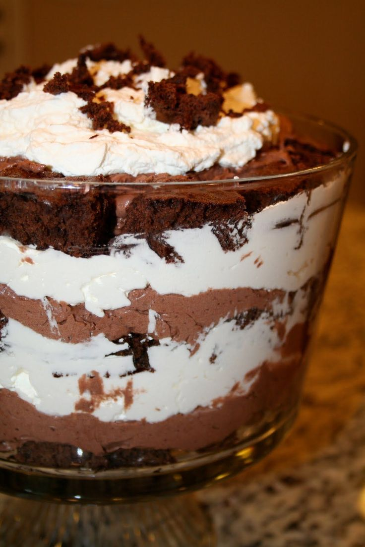 Chocolate Mousse Trifle: 1 19.8 oz. package brownie mix (use one with chocolate chips in it!) , 16 oz. heavy whipping cream , 1/4 cup sugar , 1 tsp. vanilla , 1 3.9 oz. package instant chocolate pudding mix , 1/2 cup water , 1 14 oz. can sweetened condensed milk , Chocolate Candy Bar, to shave and put on top