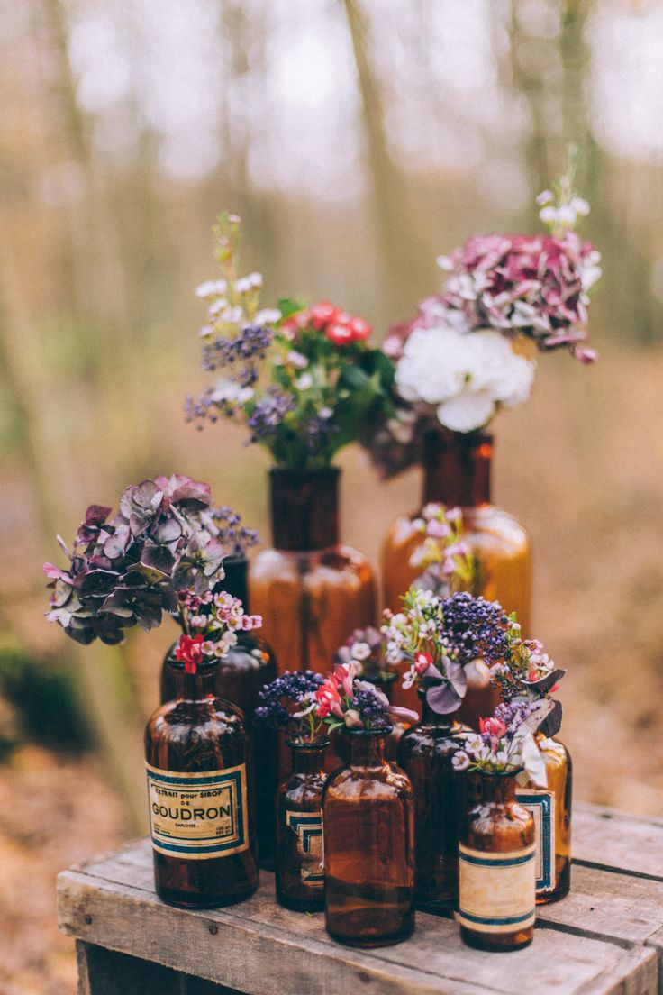 Glass Bottles & Flowers Wedding Decor - Vintage Inspired Wedding Inspiration From A French Forest With Images by Juli Etta Photography and Styling by Olivia Pellerin