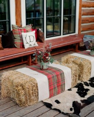 Simple hay bales are dressed up with cowhide rugs, plaid pillows and aztec throws, perfect for keeping warm outdoors after the sun sets.