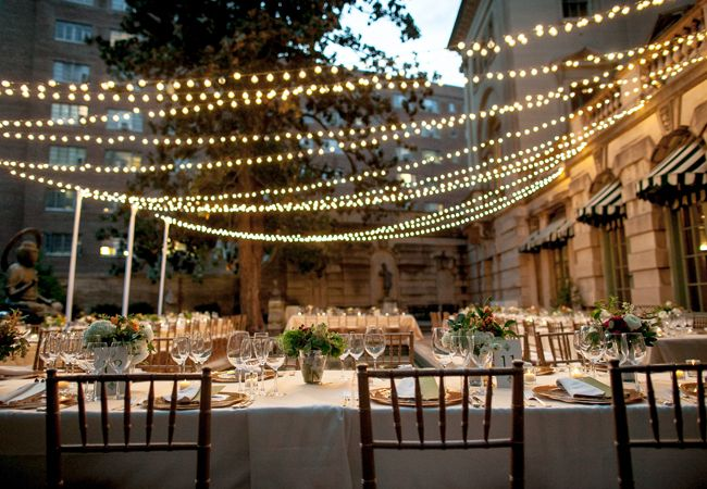 String lights over the dining area of an outdoor evening wedding to give it an intimate glow