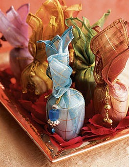 Candles wrapped in colorful silk pouches with mini tassels are a beautiful wedding favor.