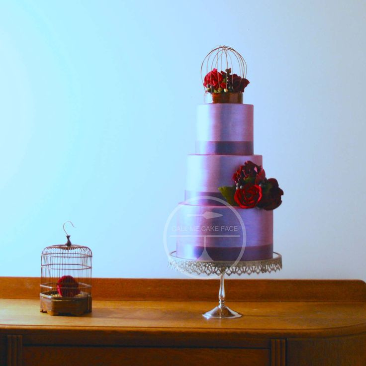 Classic style wedding cake finished in violet lustre and adorned with red sugar roses.  Topped with a hand made bird cage filled with red sugar roses.
