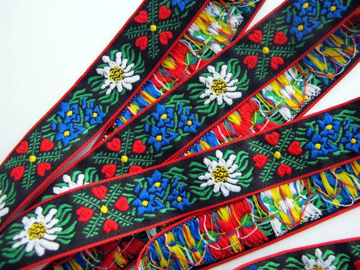 EDELWEISS & cuori Jacquard trim. Bianco, blu, rosso, verde e giallo su nero. Bordi rossi Larghezza media di 2-A #949  Un grande nastro tirolese. Vestito bavarese trim  1 di larghezza (25mm).   Qui offerti sono 3 cantieri continui di un bel modello tirolese nastro Jacquard. Molto dolce. Con fiori bianco EDELWEISS, blu e giallo con fogliame verde e i gruppi di quattro piccoli cuori rossi sfondo nero. Con rosso tessuti bordi rifiniti. (1 yarda = 91,5 cm).  Lavare in ciclo delicato fred...