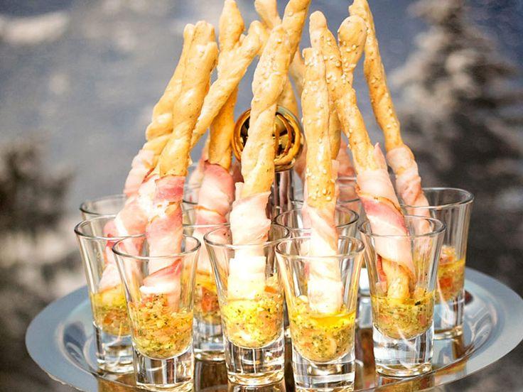 Удивите гостей оригинальной подачей простых продуктов, приготовьте закуску «китайские палочки». Для ее приготовления потребуется упаковка обычной соломки и 300 г красной слабосоленой семги. Рыба нарезается тончайшими ломтиками и на каждую соломинку накручивается внахлест. При необходимости основание соломки можно перевязать перышком зеленого лука.Так же  можно подать тонко нарезанную ветчину, а вместо соломки использовать сырные палочки. Подают такие палочки, поставив их в стаканы.