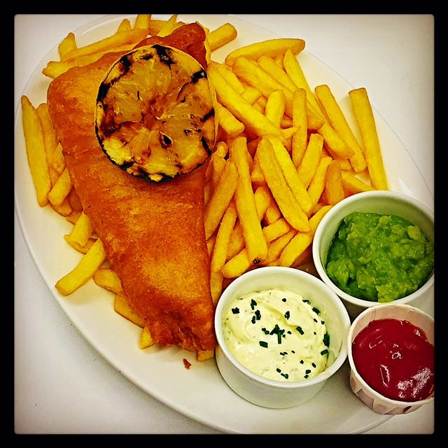 Pride of Britain's Fish and Chips: Experience the best of British with our traditional tempura battered white fish, served with fries, mushy peas, mixed leaf salad, tartar sauce & a grilled lemon wedge.