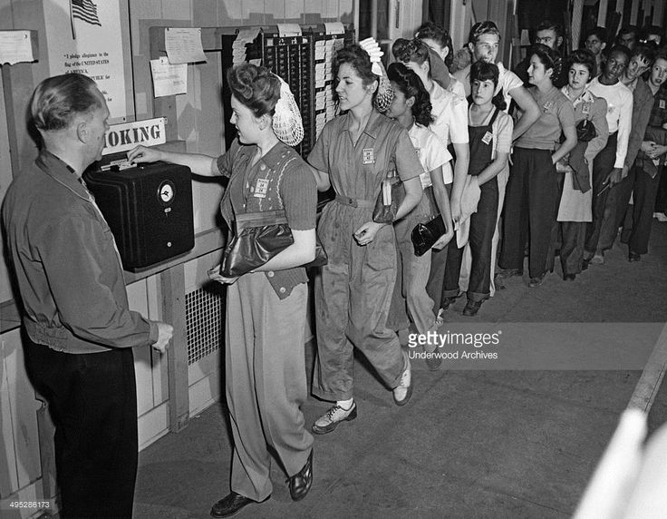 Students at James A, Garfield High School in LA check in at the time clock for their work at the high school airplane plant, Los Angeles, California, December 10, 1943.