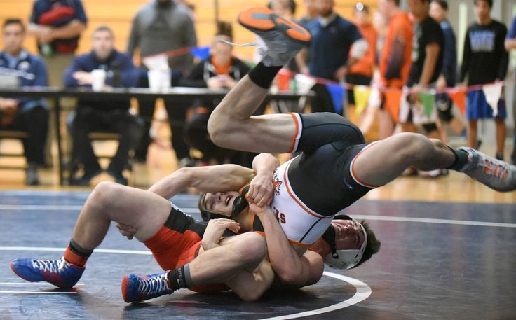 St. Charles East's Anthony Rubino (top) and Glenbard East's Drew Fugiel in the 126-pound semifinal match in the Upstate Eight wrestling meet at West Chicago High School Saturday.