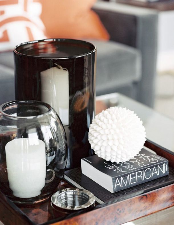 A serving tray accompany by candle holders, with layers of books top by simple accessories can transform any coffee table or ottoman.