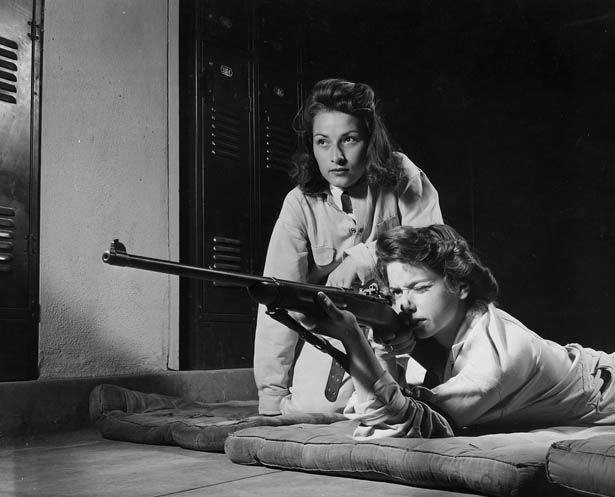 1950s: Two students from Roosevelt High School in Los Angeles, who, under the guidance of the Victory Corps, are learning how to operate a rifle.