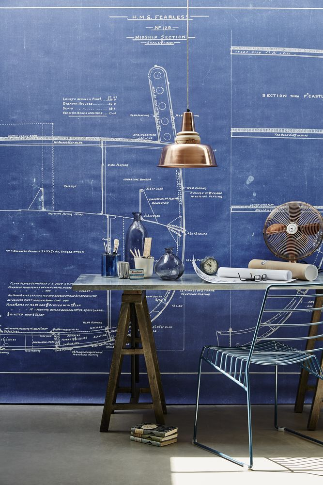A blueprint wall mural is a quirky backdrop for an industrial-style workspace. Smoky-tinted vases soften the metal surfaces. For more home office ideas visit housebeautiful.co.uk