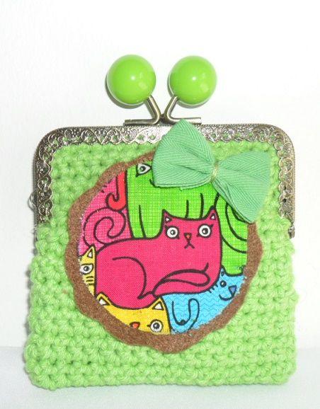 Carteira feita em linha barbante na cor verde claro. Fecha com fecho metálico e a decorar tem uma aplicação em feltro com gatinhos e um laço verde em tecido. Tamanho aproximado: 10cm x 12 cm Preço: 5€