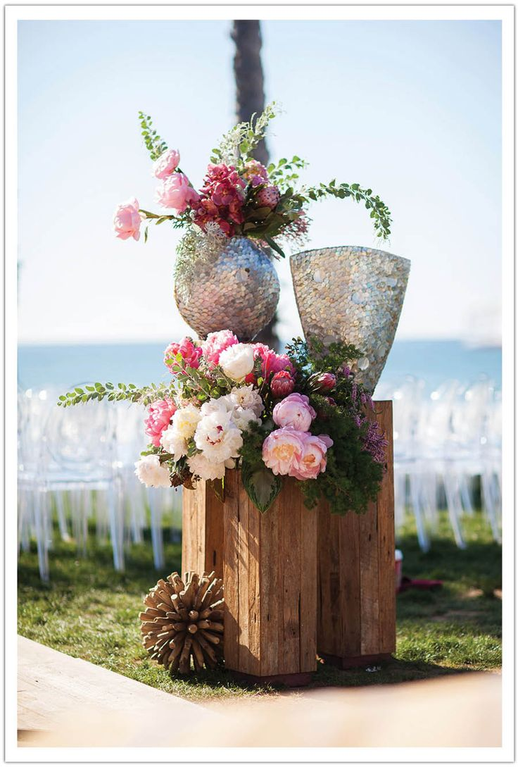 rustic wood pillars with mother of pearl vases boasting underwater inspired flowers including pink peonies, orchids, wild greenery and other textures emulating an underwater wild coral reef.  Modern Luxe La Jolla Beach Wedding by Alchemy Fine Events, part 1 www.alchemyfineevents.com