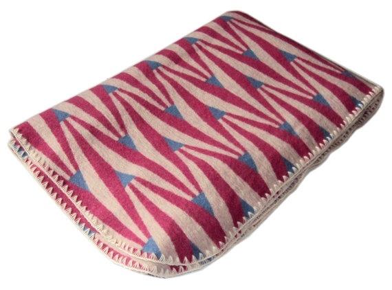 Stickad filt 100% merinoull. Mönstrad i rosa, ljusblått och oblekt. på Nordic Design Collective