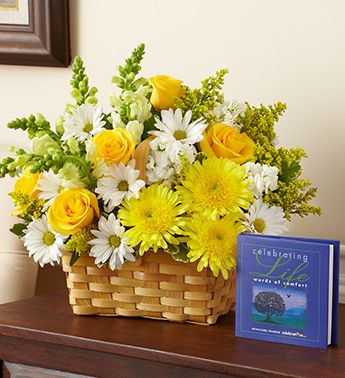 Remember a beautiful life in a truly original way. A vibrant yellow and white sympathy basket arrangement of roses, snapdragons, cremones, stock and more offers comfort during times of loss, while the keepsake book Celebrating Life, by Jim McCann brings lasting memories and reflection.