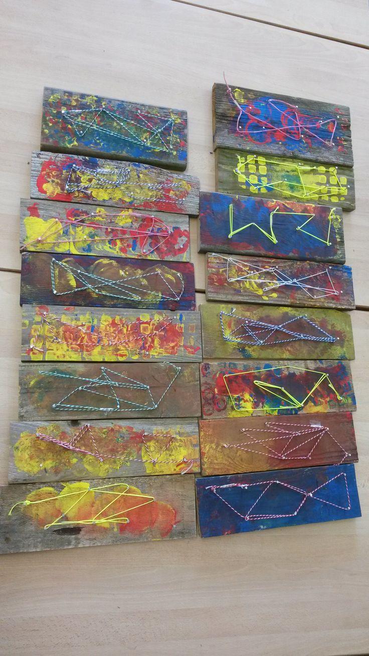 Houten plankje door de kleuters laten schuren, bestempelen, (zelf spijkers in getimmerd) en hen deze laten verbinden met een gekleurd touw
