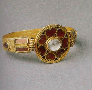 Bracelet - Kerch, the Crimea - Late 4th-early 5th century AD - Gold, garnet, rock crystal - Diam 6 cm, wt 129.28 g - This bracelet is an example of the cloisonné technique, widely used during this period. It consists of a gold hoop, linked by means of hinges to a round medallion. The medallion and the ends of the hoop are decorated with garnet and rock crystal inlays.