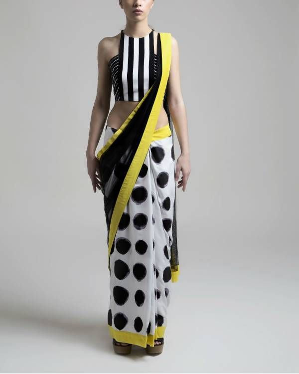 Net polka saree    Combination of a sheer fabric with the fluidity of cotton modal. The yellow borders add to the charm of the sari.