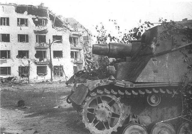 A Sturmpanzer IV of Sturmpanzer-Kompanie 218 z.b.V sits in front of the ruins at ul. Mickiewicza 18.