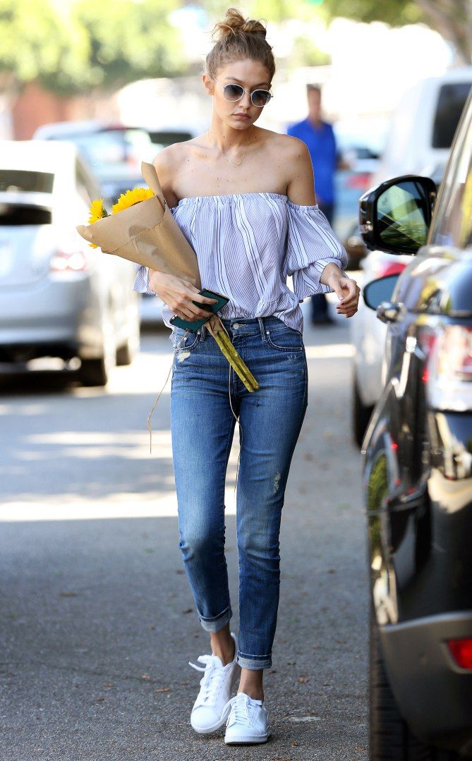 Gigi Hadid in a blue off-the-shoulder top, skinny jeans and white sneakers - click through to see more celebrity summer outfit ideas!