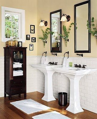 Yellow Bathroom With Double Pedestal Sinks Minus Dark Wood Accents