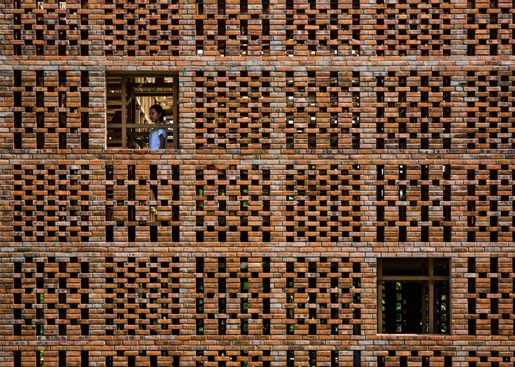 Pottery studio hides elaborate bamboo shelving grid behind its perforated brick walls