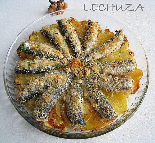 SARDINAS AL HORNO  con patatas /  12 xoubas (sardinas pequeñas). 2 patatas. 1 cebolla. dos dientes de ajo. perejil. Pan cracker de Harinas Sta. Rita. aceite y sal