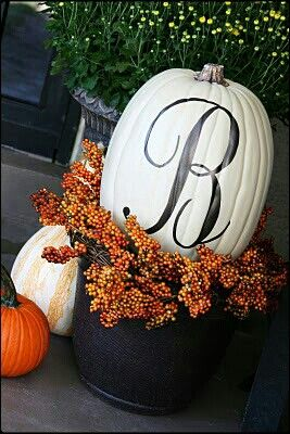 Fall/Halloween front porch/door ideas. Inspiration. Love the large white pumpkin with the painted initial tucked inside of an Autumn wreath in a flower pot, instead of the standard mums.