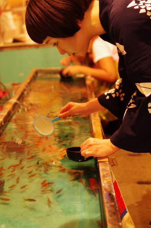 Goldfish-scooping game (Kingyo sukui) at the summer carnival. 金魚すくい