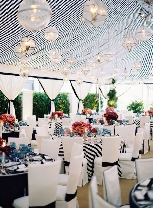 navy striped wedding linens and tent with chandeliers and pink bouquets