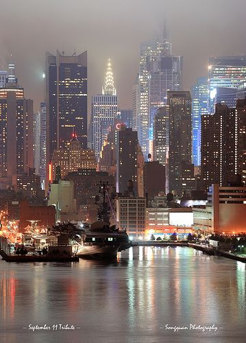 New York City Manhattan midtown skyline at night with skyscrapers over Hudson River viewed from New Jersey.