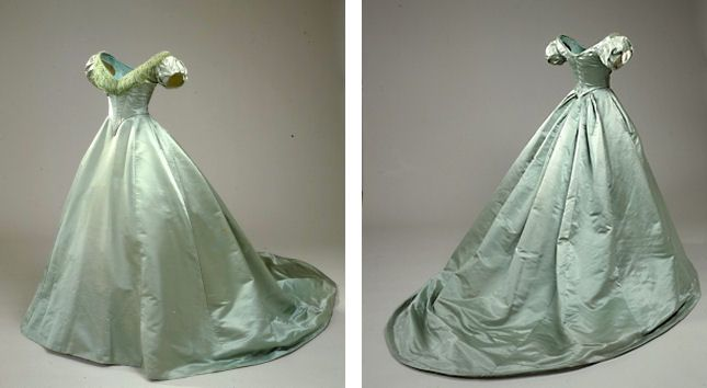 Evening dress, 1856, 2 piece, sea green taffeta. The bodice has a low neckline with ruched tulle at the front, short pleated puff sleeves, corded back (corset style). The skirt is made of eight panels with a flat front and longish train. Preserved at the National Museum of History, Copenhagen.