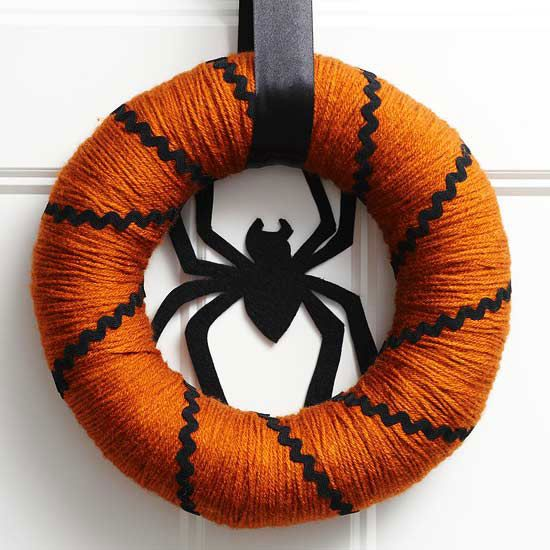 Add a spooky Orange and Black Spider #Wreath to your door this season! More festive door decorations: http://www.bhg.com/halloween/indoor-decorating/halloween-door-decor-28-great-ideas/
