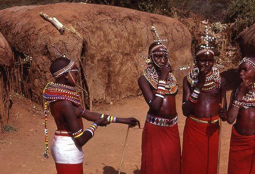 Het zijn Afrikanen met een donkere huidskleur , ze dragen kleurrijke kleding
