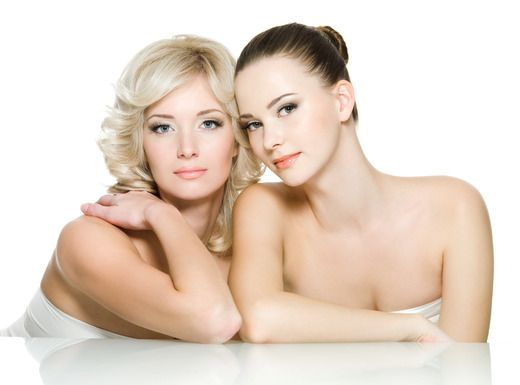 Sensuality faces of two beautiful young adult women are together. Girls posing on white background