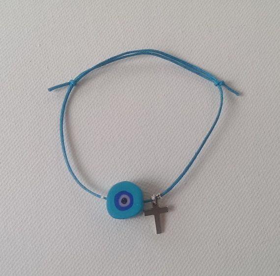 Bracelet decorated with handmade polymer clay evil eye and silver plated metal cross. Baptism, christening