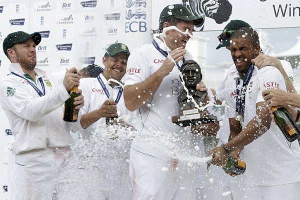 South Africa cricket captain Graeme Smith, holds the winners trophy as he is doused with champagne after they defeated England at Lord's Cricket ground. (AP)