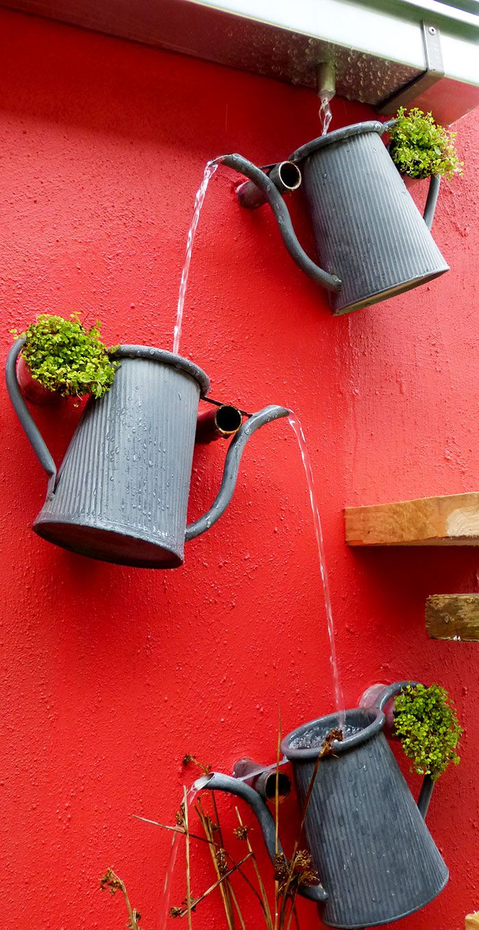 Fantastic cascading watering can feature. Great way to create a decorative drainage system from the guttering. And it looks so sweet!
