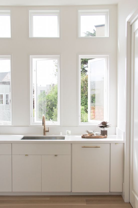 Lovely Kitchen Features Vertical Windows In Lieu Of Upper Cabinets Over A  White Flat Front Cabinets Adorned With Gold Hardware Fitted With A  Stainless Steel ...